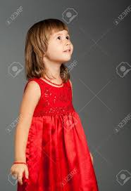 cute four year old in a red dress looking up stock photo