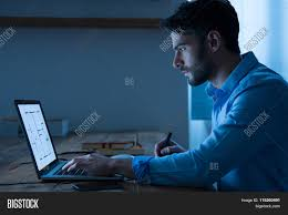 Blueprint Of A House Sitting At Night Working On Architectural Plan On Laptop Young