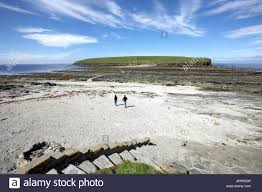 two people walking to the brough of birsay orkney islands scotland