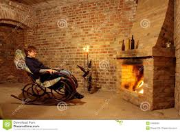 woman in rocking chair by the fireplace with candl royalty free