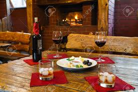 romantic dinner for two near fireplace wine and cheese plate