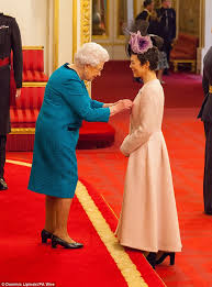 queen elizabeth ii beams after winning a a 98 voucher from helen mccrory beams as she collects her obe daily mail online