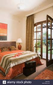 Spanish Bedroom Furniture by Faux Fur Throw On Bed With Orange Bedlinen In Spanish Bedroom With