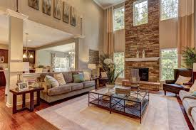 windows flank a soaring stone fireplace in this two story great