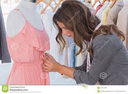 fashion designer measuring dress on a mannequin royalty free stock