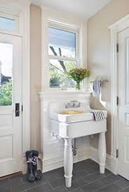 furniture pedestal laundry sink with towel bars and floor tile