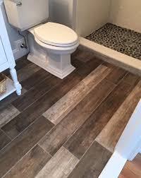 spa like bathroom renovation wood grain tile pebble shower floor