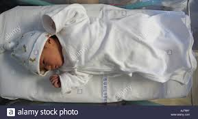 Baby Sleeping In A Crib by Newborn Baby In A Hospital Crib On The Day Of Birth Stock Photo