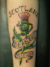memorial thistle flower with banner tattoo design for arm by