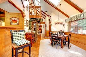 bright kitchen and dining room in log cabin house high vaulted