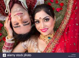 wedding dress up for indian and groom in traditional wedding dress and posing