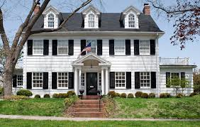 traditional american home white exterior with navy blue shutters