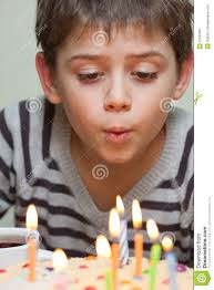 blowing candles young boy blowing out candles on birthday cake