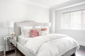 light pink and white bedding gray camelback headboard with pink flower pillows transitional