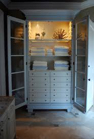 large white storage cabinet ceiling to floor cherry finished wooden cabinet with open shelves