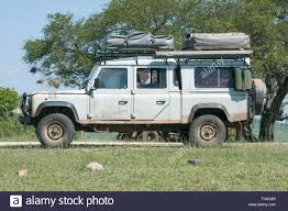 british land rover defender old land rover defender 110 with two roof tents parked at roadside
