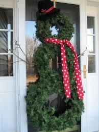 snowman wreath maybe on brick between garage doors decor
