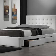 queen size bed with white leather headboard and there are storage