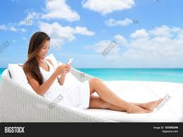 Beach Lounger Using Phone App Relaxing On Sun Bed On Outdoor Terrace Home