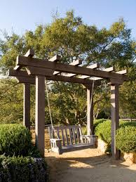 pergola swing plans a lovely wooden arbor with attached swing is bordered by