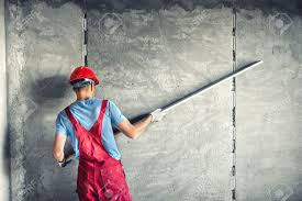 industrial worker with plastering tools renovating a house