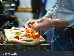 knives in the kitchen man cleans onion kitchen knife kitchen stock photo 559468270
