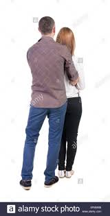 back view of young embracing couple man and woman hug and look