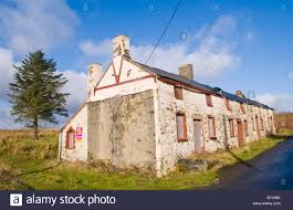 boarded up derelict row of 4 terraced stone cottages for sale by