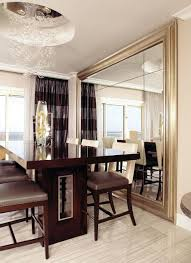 comely dining room with glossy black table and big wall mirror