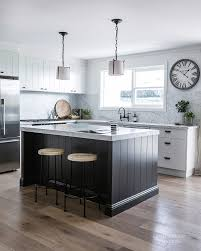 modern farmhouse kitchen white cabinetry with black island in a v