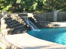 a fountain in a modern home backyard with swimming pool also