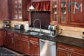 Baltic Brown Granite Countertops With Light Tan Backsplash by Grey Granite Countertops With Cinnamon Cherry Cabinets Tan Brown
