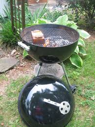 barbecue master grilling on the weber kettle with a meadow