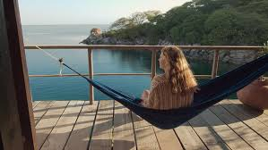 4k woman sitting in hammock relaxing on deck of exotic
