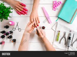 nail care closeup of female hands filing nails with professional