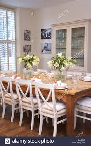 white painted chairs at plain wood table in country dining room