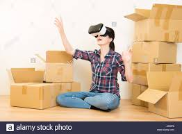 young woman sitting floor of new house planning home with vr