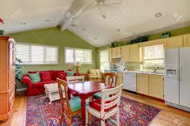 colorful room with green wall yellow kitchen cabinets and bright
