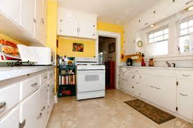 white old small simple kitchen interior with yellow walls stock