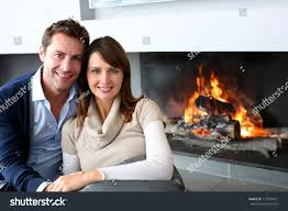 romantic couple sitting by fireplace home stock photo 115953421