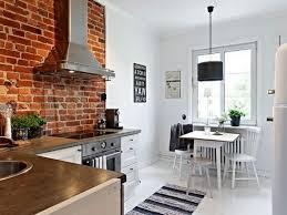 exposed brick kitchen backsplash brown wooden pedestal countertop