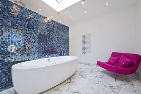 stylish bathroom with armless sofa and freestanding tub also blue