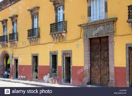 a colonial style house painted yellow and red in san miguel de