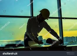 silhouette builder engineer wear security helmet stock photo