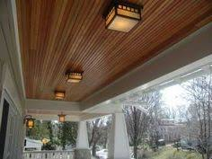 dark stained beadboard on the ceiling of covered patio making a