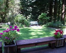 Backyard Corner Landscaping Ideas by Spacious Backyard With Red Flowers On Interesting Planter Plus