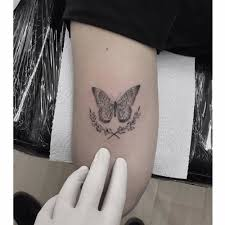 small line butterfly on the back of the left arm artista