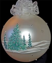 photo of glass ornament with painted snow covered pine trees