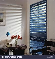 sunlight coming through blue venetian blind in white study with