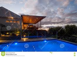 modern hotel with a pool at night with light sky stock photo